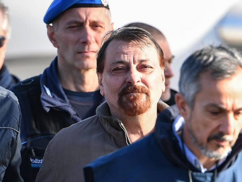 Italian former communist militant Cesare Battisti (C), wanted in Rome for four murders attributed to a far-left group in the 1970s, is escorted by Italian Police officers after stepping off a plane coming from Bolivia and chartered by Italian authorities, after landing at Ciampino airport in Rome on January 14, 2019. Former communist militant Cesare Battisti landed in Rome on January 14 after an international police squad tracked the Italian down and arrested him in Bolivia, ending almost four decades on the run.  / AFP / Alberto PIZZOLI